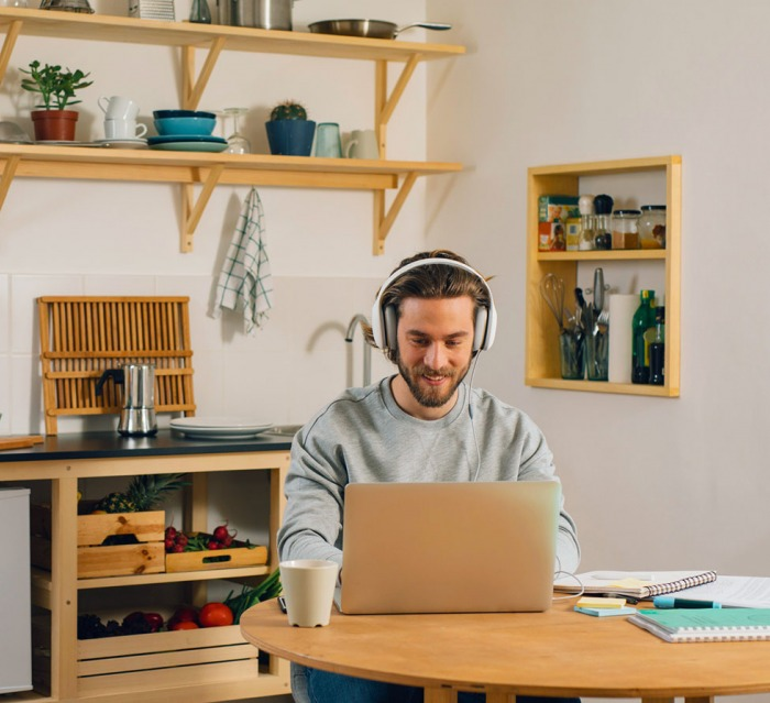 Young Caucasian man with headphones using his laptop at the kitchen table.