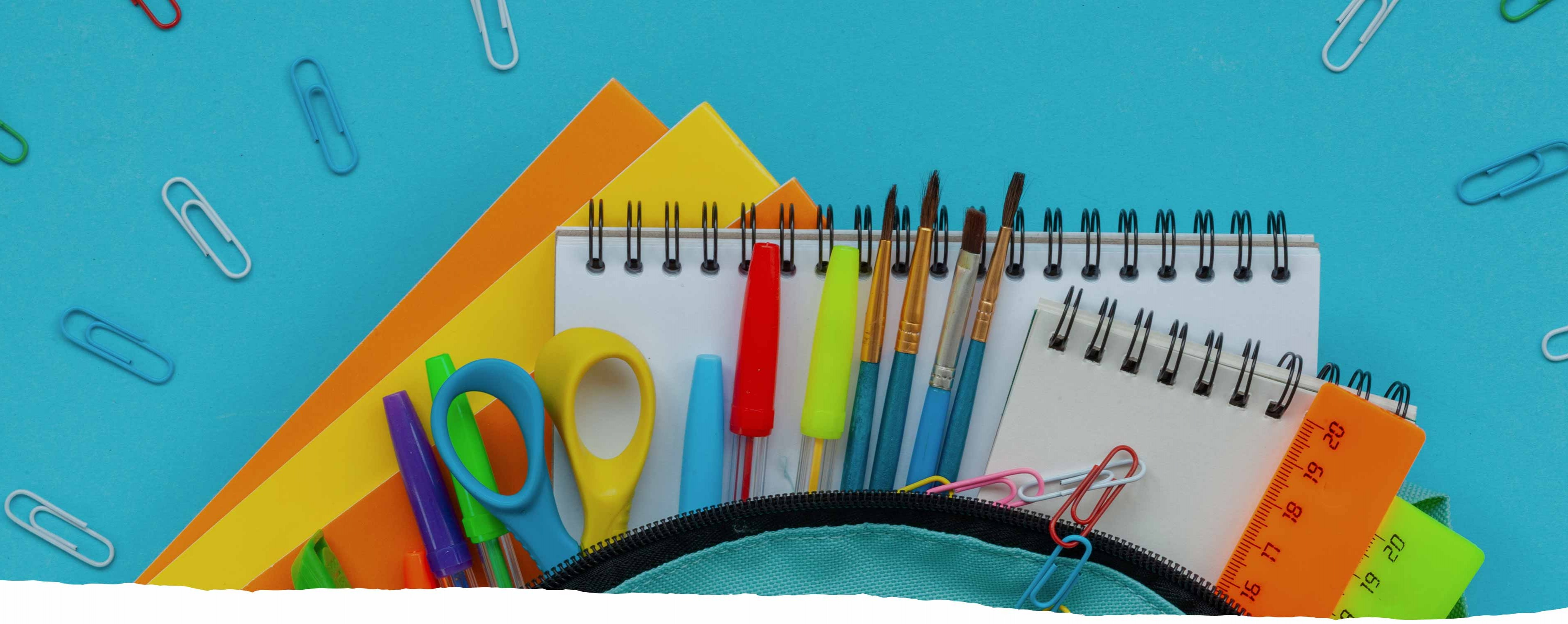 School supplies spilling out of a backpack, such as scissors, paperclips, pens, paintbrushes and a notebook.