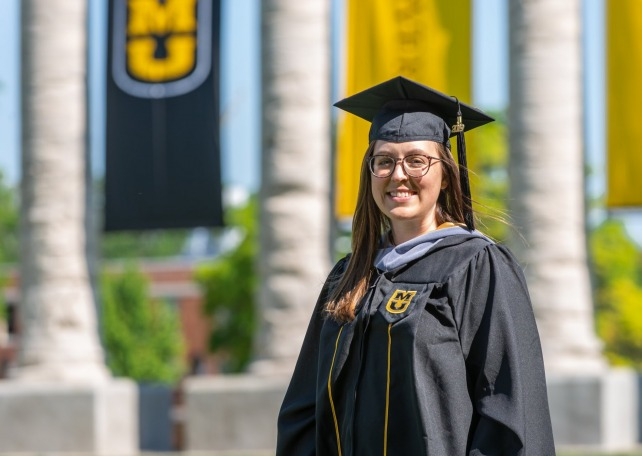 Stephanie Gillam, biomedical sciences MS, wearing a graduation cap and gown in front of Mizzou's columns.