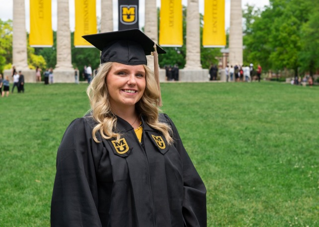 Sarah Swoboda, bachelor's in business administration '19, wearing her graduation cap and gown, with the Mizzou columns behind her.