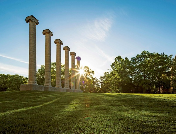 The sun shining through the columns on the Quad on Mizzou's campus.
