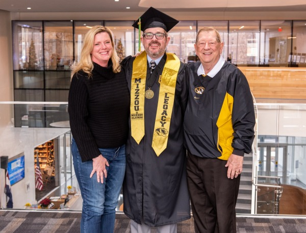 Neil Schmedding, BHS, wearing his graduation cap and gown, standing next to his sister and father, who are both Mizzou graduates.