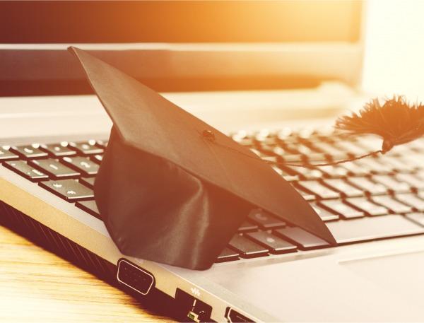 Graduation cap on top of laptop.
