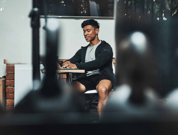 Man in guy sitting at table working on a laptop