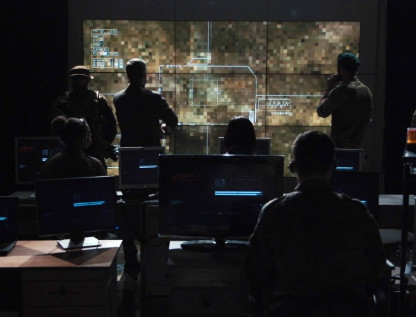Military personnel watching drown footage on a large screen in a dark command center style room.