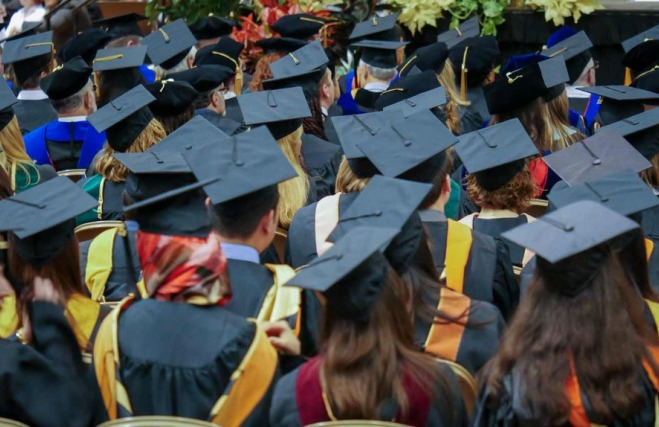 Students in graduation caps at a Mizzou commencement ceremony.