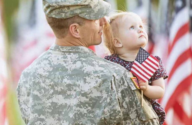 Military hero and child standing by American flags.