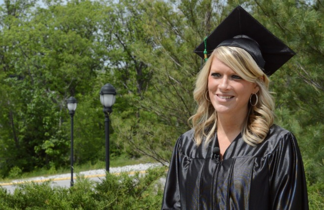 Graduate Alicia Reed on Mizzou's campus wearing graduation cap and gown.