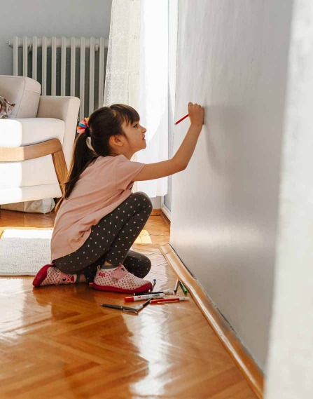 A child drawing on a wall.