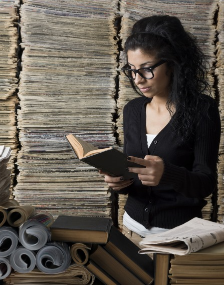 a female archivist studies a small book, surrounded by towers of newspapers
