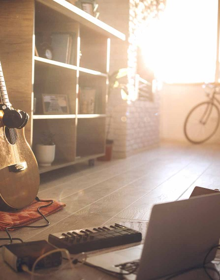 A room with a laptop and guitar.