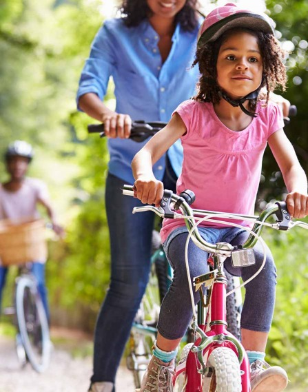 A child and parent riding bikes in a park.