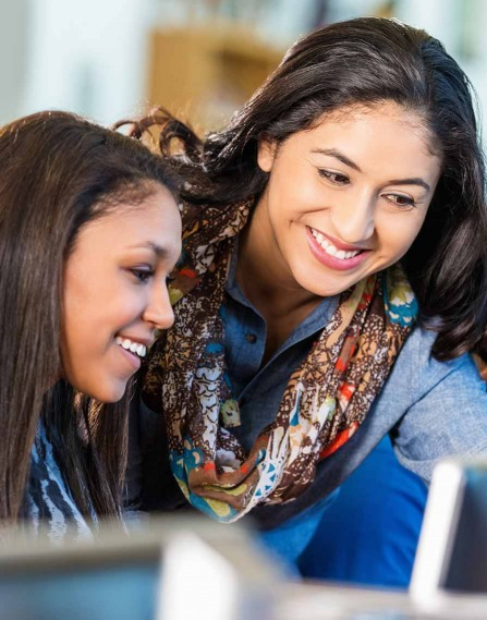 two women looking at a desktop monitor together and smiling