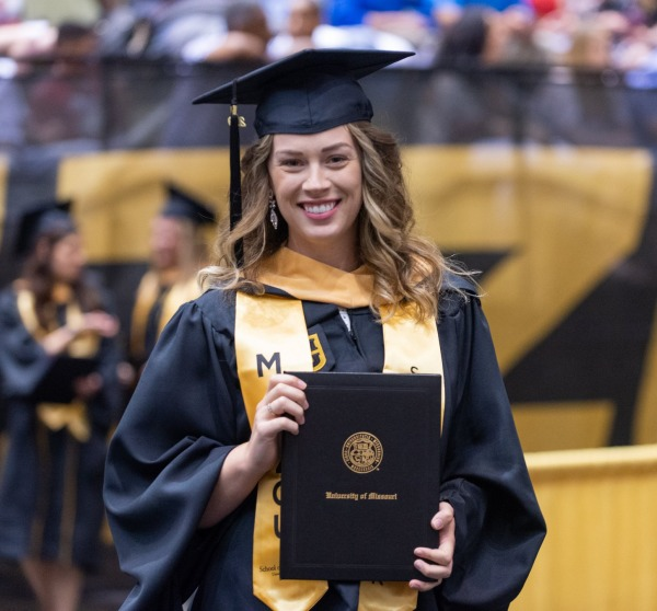 Chelsea Hoyer, MSW, wearing her graduation cap and gown and holding her diploma at her commencement ceremony.